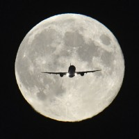 "A passenger aircraft, with the full ""Harvest Moon"" seen behind, makes its final approach to landing at Heathrow Airport in west London"
